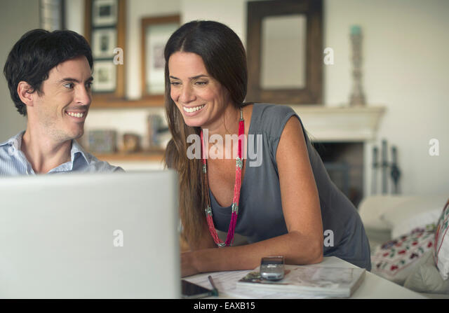 Couple using laptop computer at home - Stock Image