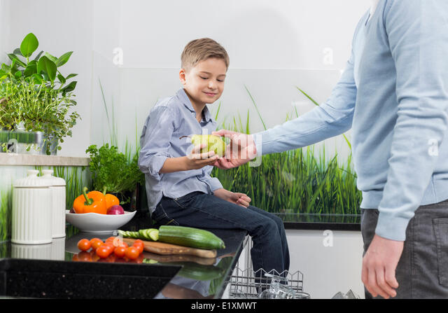 Midsection of father giving pear to son in kitchen - Stock Image