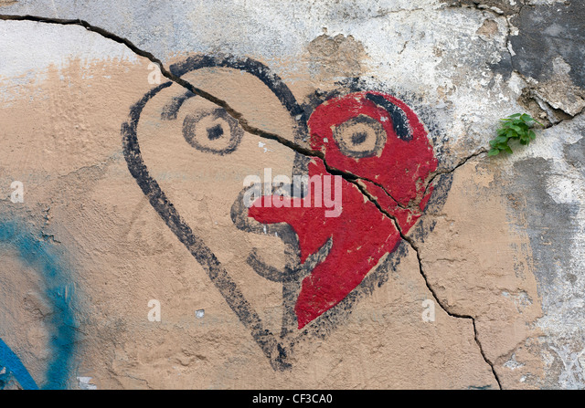a crack through a painted heart resembling a face on a wall - Stock Image