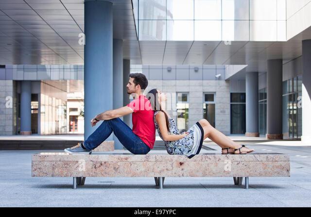 Female student leaning against her boyfriends back - Stock-Bilder