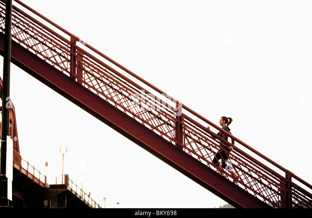 An athletic female in a purple jacket running stairs in Portland, Oregon. - Stock Image