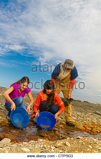 Local prospector teaching visitors how to pan gold near Nome, Arctic Alaska, Summer - Stock Image