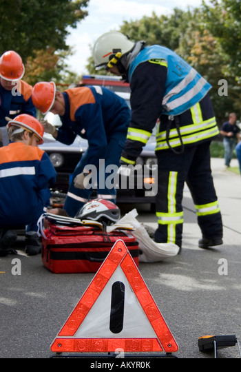 A youth fire brigade shows what to do at an scene of an accident - Stock Image