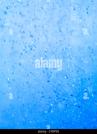 Closeup of blue spraying water droplets abstract blue background texture - Stock Image