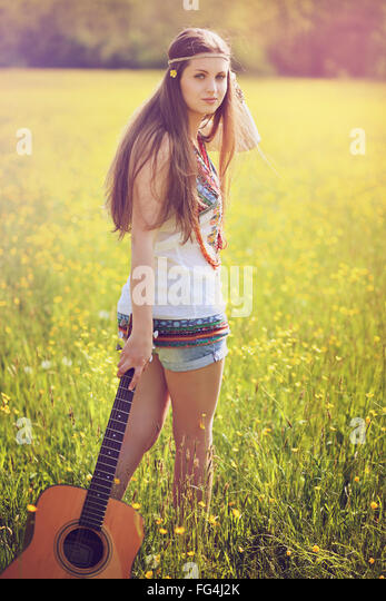 Beautiful hippie woman with guitar . Summer colors portrait - Stock Image