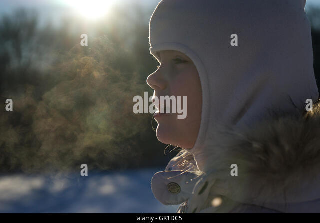 close up of child in snowsuit. winter scene, blur, kid, hood. - Stock Image