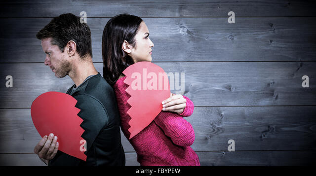 Composite image of serious couple standing back to back - Stock Image
