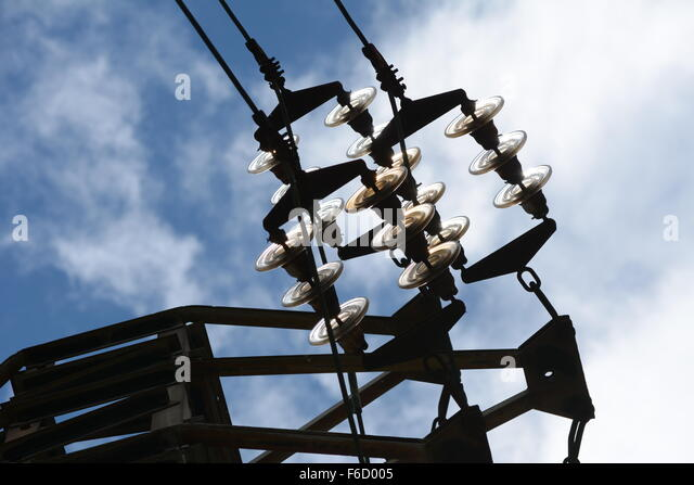 High Voltage cable connectors and glass isolators against blue sky with clouds - Stock Image