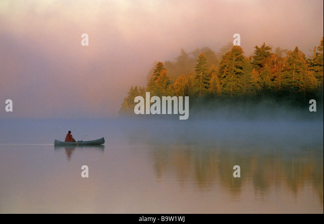 Canoeing on misty morning Quetico Provincial Park Ontario Canada - Stock Image