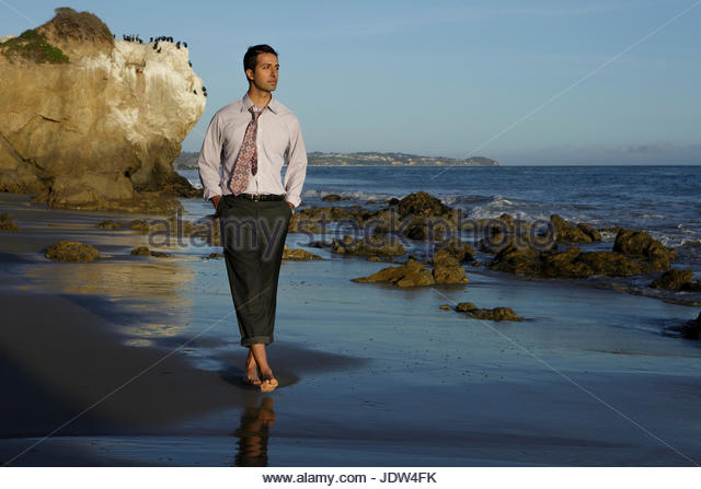 Businessman walking on El Matador beach, California, USA - Stock-Bilder