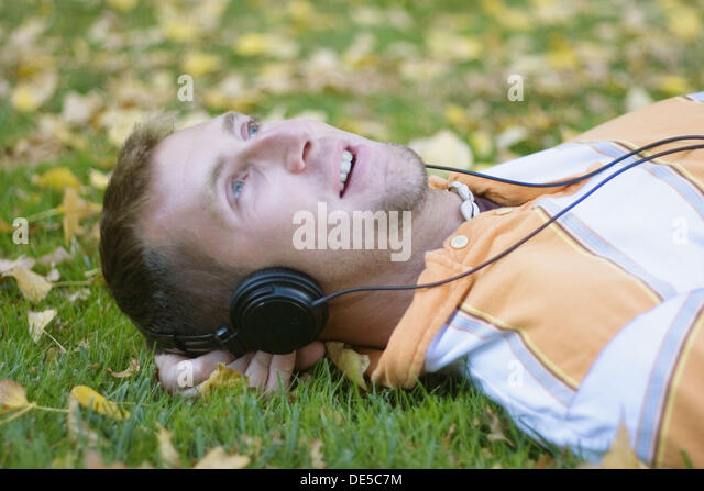 A young man laying on grass while listening to music on his headphones - Stock Image