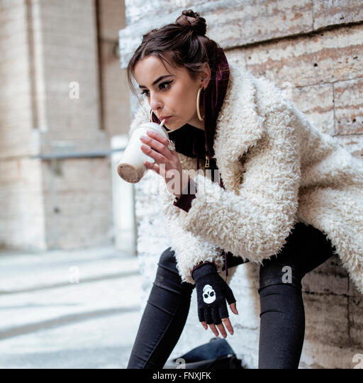 young pretty stylish teenage girl outside on city street fancy fashion dressed drinking milk shake - Stock Image