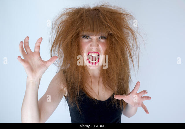 Woman with messy tangled long brown hair about to fight screaming - Stock Image