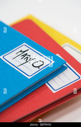 Pile of school notebooks with name written on label - Stock Image