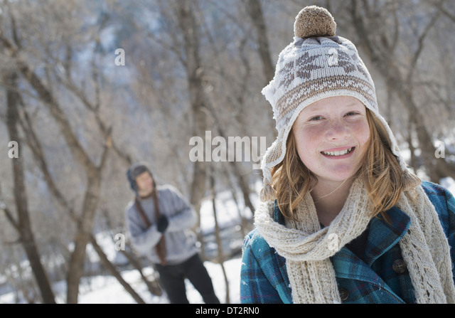 Winter scenery with snow on the ground A young girl with a bobble hat and scarf outdoors A man in the background - Stock Image
