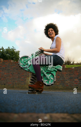 Happy, laughing woman playing on bouncing playground equipment - Stock Image
