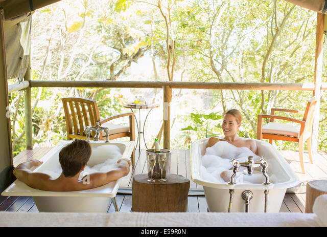 Couple in twin bathtubs in outdoor spa - Stock Image
