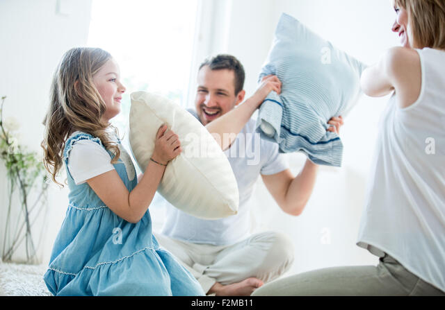 Family having fun with pillow fight - Stock Image