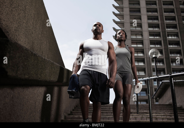 Fit young couple in running wear walking down steps on city estate - Stock-Bilder