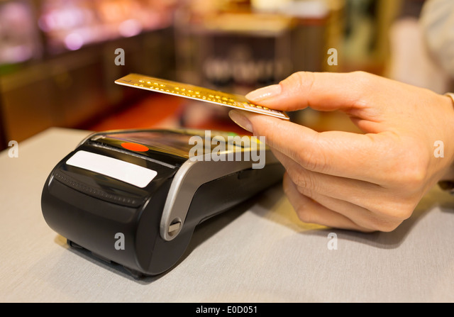 Female paying credit card shop butcher - Stock Image
