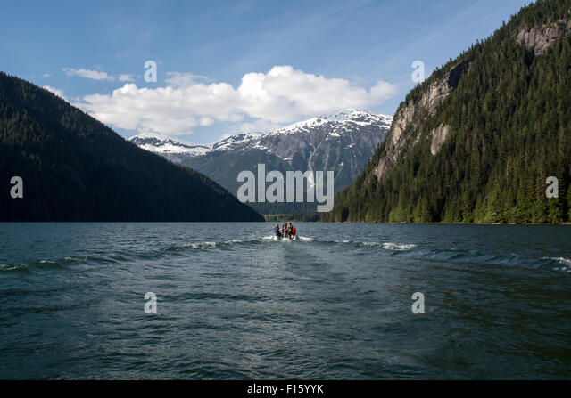 A wilderness guide and tourists travel up a remote lake by zodiac in the Great Bear Rainforest of British Columbia, - Stock-Bilder