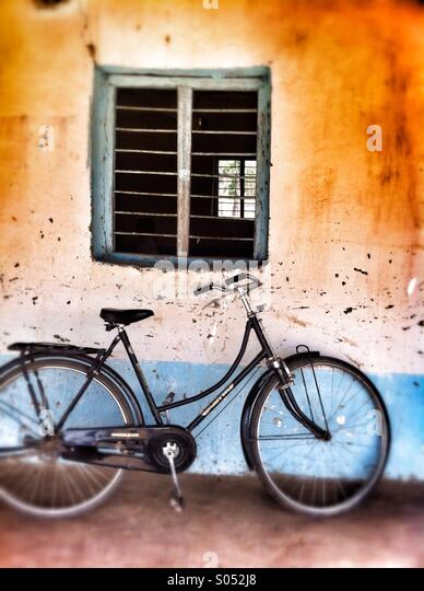 Bicycle leaning on wall in rural village in India. - Stock Image