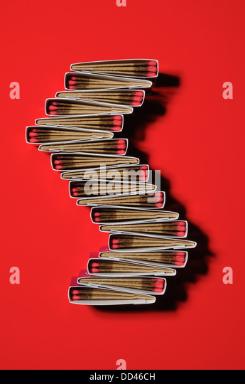 Packs of matches together forming a unique pattern. s shape, red background - Stock Image