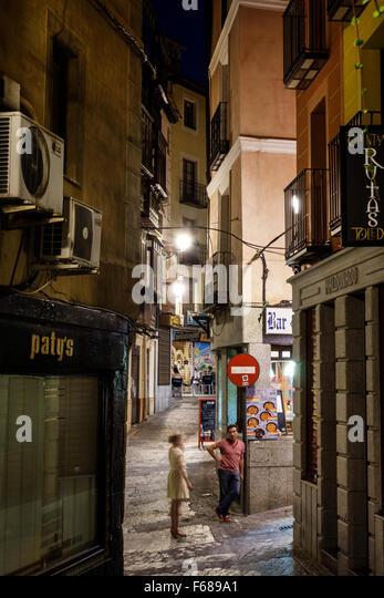 Spain Europe Spanish Hispanic Toledo dusk night nightlife Plaza Solarejo man woman couple buildings - Stock Image