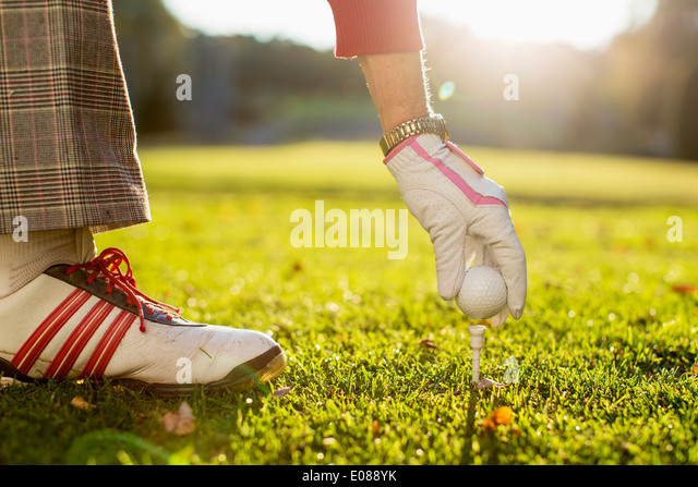 Cropped image of senior woman placing golf ball on tee - Stock Image