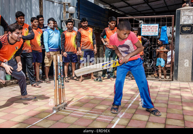 India Asian Mumbai Lower Parel Dhuru Wadi Sitaram Jadhav Marg box cricket game charity event bat player man boy - Stock Image