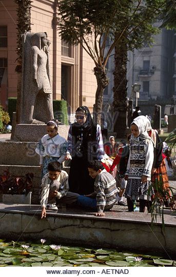 Egypt Cairo Egyptian Museum female Muslim students heads covered males Sphinx statue - Stock Image