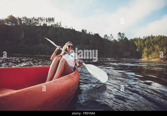 Young woman kayaking on a lake. Happy young woman canoeing in a lake. - Stock Image