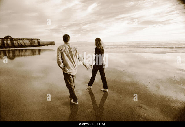 Couple enjoying a soulful sunset stroll in black and white - Stock Image