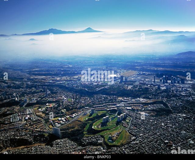 aerial view above morning fog Interlomas Golf Course Santa Fe to volcanoes Iztaccihuatl and Popcatepetl Mexico City - Stock Image