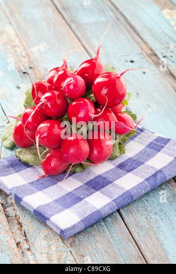 Close up of red radish bundle on checked napkin - Stock Image