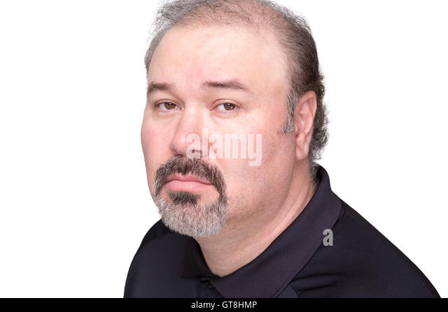 Close up of downcast middle aged male in black shirt with graying beard and mustache over white background - Stock Image