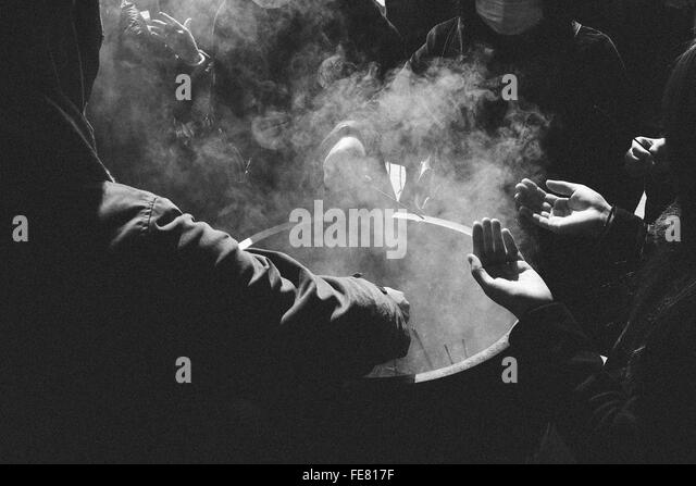 Group Of People Around Smoke Container - Stock Image