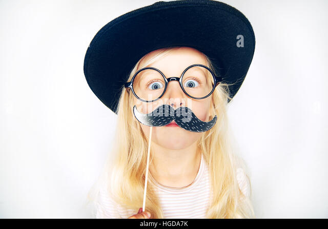 Little girl wearing black hat and glasses holding fake moustache on stick and looking at camera. - Stock Image