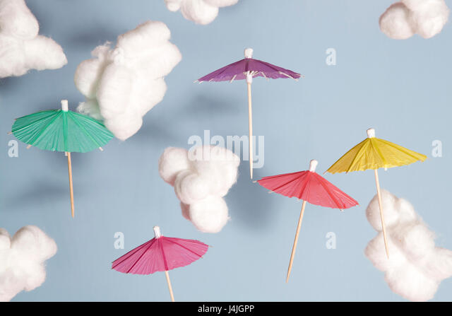 Color cocktail umbrella flying in the air between cotton wool as cloud Blue background - Stock Image