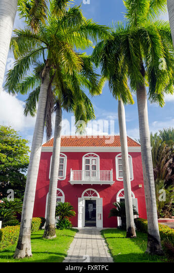 Red Dutch colonial-style building with tall palm treesbeside the sidewalk, Willemstad Curacao - Stock Image