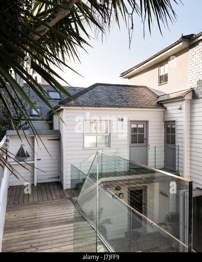 Contemporary glass balustrades and wooden decking on New England style deck of cornish holiday home. Doors painted - Stock Image