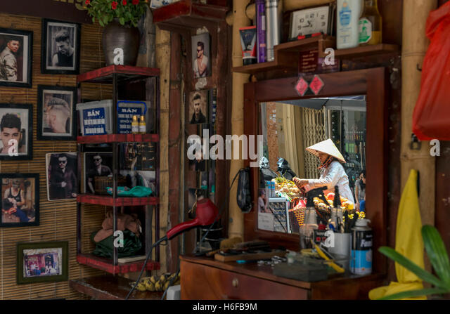 Reflection of a fruit seller on the mirror of a barber shop in a street of Hanoi. - Stock-Bilder