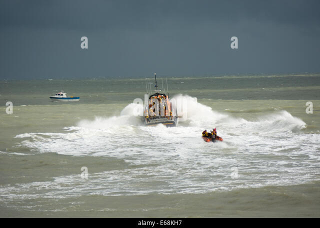 The Eastbourne RNLI lifeboats power through the waves at the end of a lifesaving demonstration at Airbourne 2014 - Stock Image