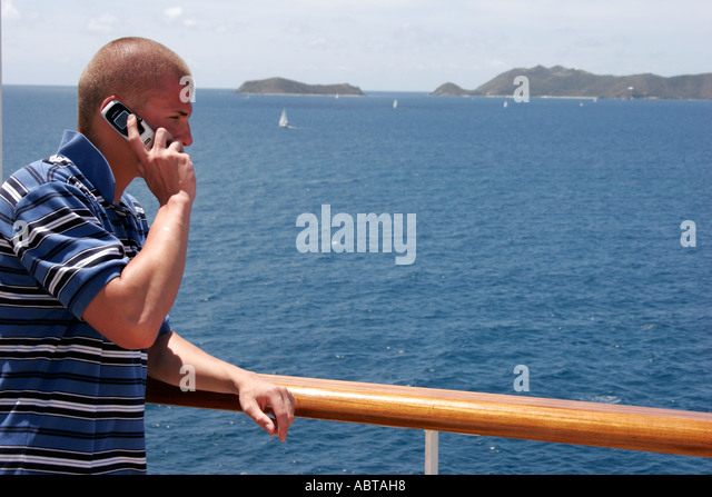 BVI Tortola Holland America Caribbean cruise ms Noordam male cell phone rail - Stock Image