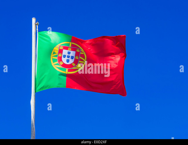Portuguese flag flying against a clear blue sky background - Stock-Bilder