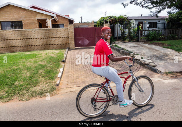 South Africa African Johannesburg Soweto Black woman bicycle bike house home - Stock Image