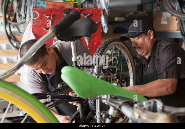Mechanics working in bicycle shop - Stock Image