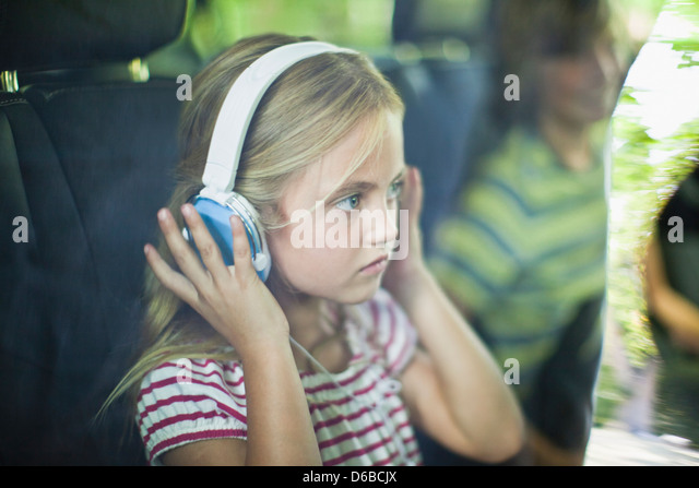 Girl listening to headphones in car - Stock Image