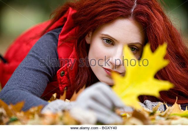 A young woman lying on the ground, looking at an autumn leaf - Stock Image