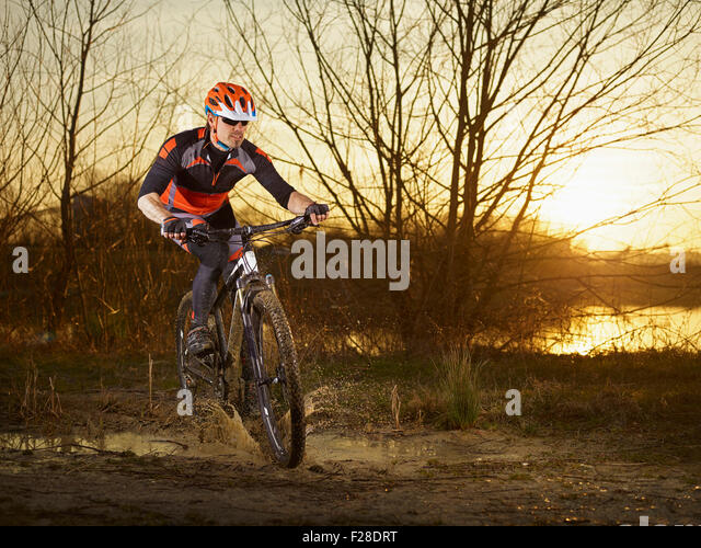 Mature man riding mountain bike on dirt track, Bavaria, Germany - Stock Image